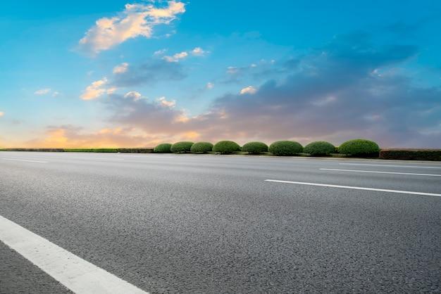 Lege asfaltweg en natuurlijk landschap in de ondergaande zon