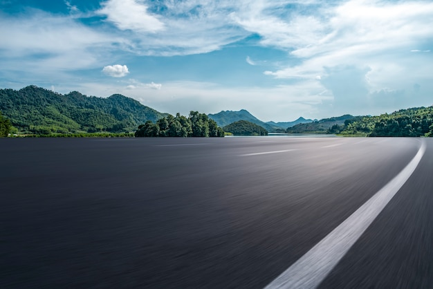 Lege asfaltweg en natuurlijk landschap onder de blauwe hemel