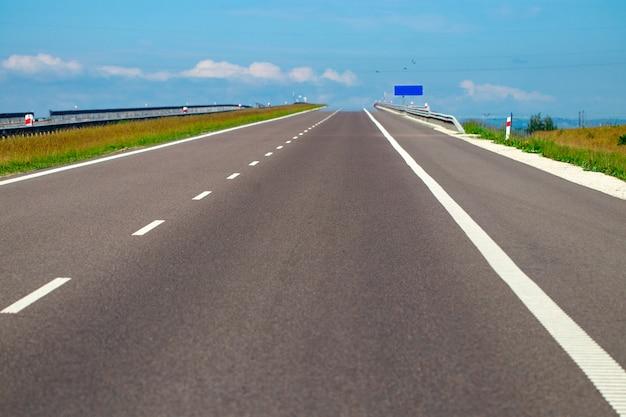 Lege asfaltweg en veld en blauwe lucht met wolken.