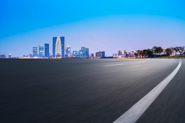 Lege asfaltweg langs moderne commerciële gebouwen in de steden van china, s