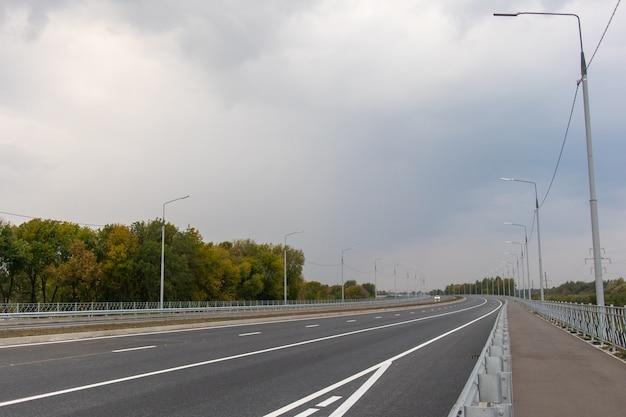 Lege asfaltweg met lantaarnpalen bij zonsondergang
