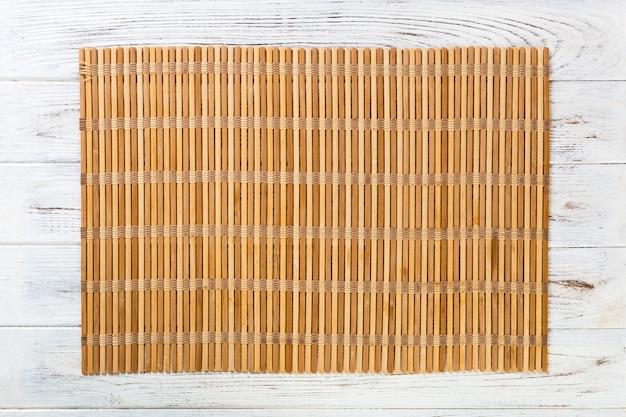 Lege aziatische voedselachtergrond. bruine bamboe mat op witte houten achtergrond bovenaanzicht met kopie ruimte plat lag