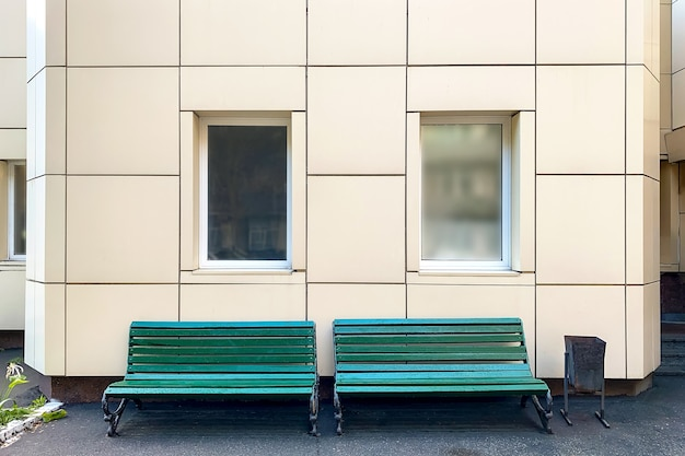 Lege bank tegen klassieke gevel met grote witte ramen in de achtertuin van het gebouw