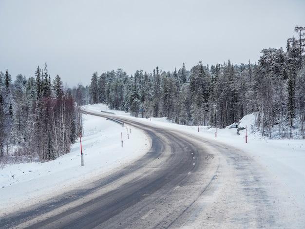 Lege besneeuwde noordelijke winterweg, zet de weg aan.