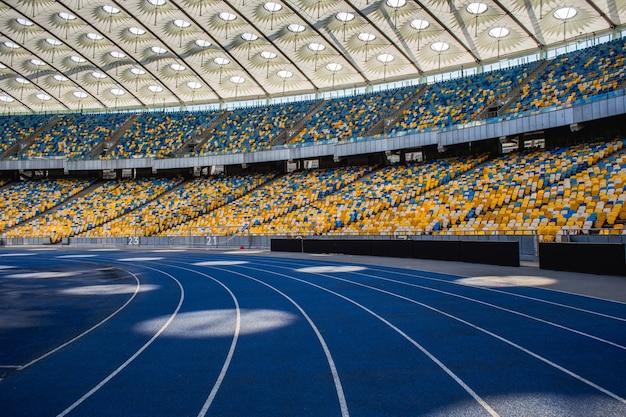 Lege blauwe atletiekbaan in het olympisch stadion tegen de achtergrond van lege tribunes