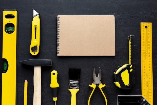 Lege blocnote en gele reparatiehulpmiddelen met exemplaarruimte