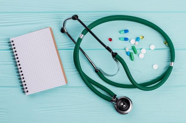 Lege blocnote met medische stethoscoop en dichtbij drugpillen die op turkooise achtergrond liggen. lege spiraalvormige blocnote.