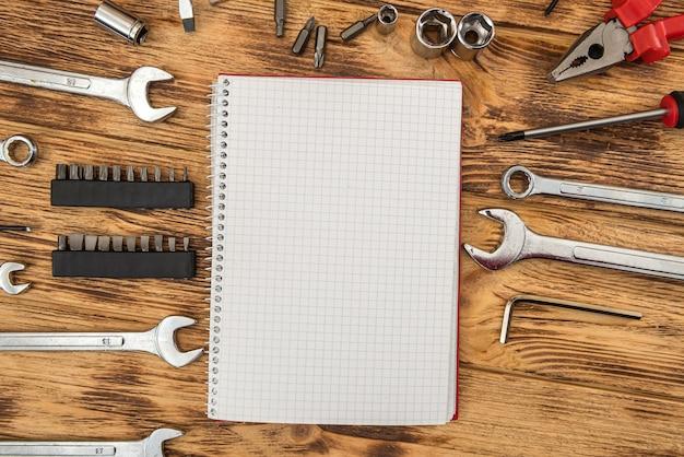 Lege blocnote omringde een reeks bouwhulpmiddelen. apparatuur voor reparatie. werkplek
