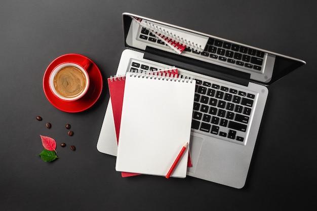 Lege blocnote over laptop en koffiekop op bureau zwarte lijst