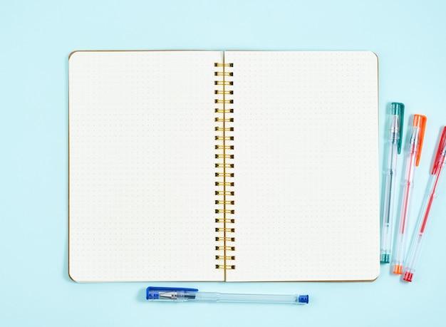 Lege blocnotepagina in kogeldagboek op blauwe bureaudesktop. hoogste mening van moderne heldere lijst