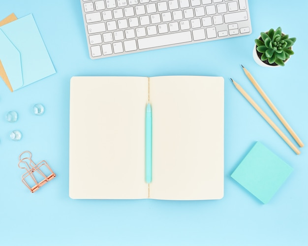 Lege blocnotepagina voor tekst op blauwe bureaudesktop. hoogste mening van moderne heldere lijst met notitieboekje