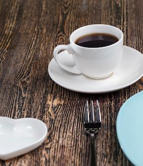 Lege borden en koffiemok op tafel, leeg glaswerk op de tafelsetting