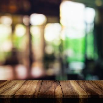 Lege bovenkant van houten tafel met vervagen interieur woonkamer voor achtergrond.
