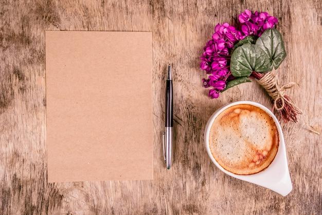 Lege brief, kopje koffie en bloemen