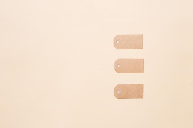 Lege bruine kartonnen prijskaartjes of etiketten op lichtbeige achtergrond. plat leggen, ruimte kopiëren, bovenaanzicht.