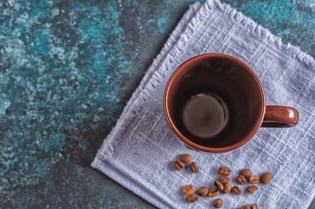 Lege bruine mok voor koffie en koffiebonen op blauwe achtergrond