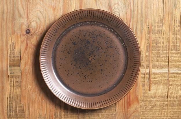 Lege bruine plaat op oude houten achtergrond, bovenaanzicht