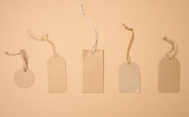 Lege bruine rechthoekige, ronde bruine papieren tag aan een touw geïsoleerd op een witte achtergrond, sjabloon voor prijs, korting