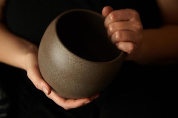 Lege ceramische bloempot in handen van een vrouw