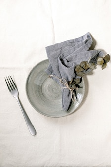 Lege ceramische plaat met vork en textielservet