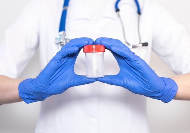 Lege container voor urineanalyse in doktershanden.