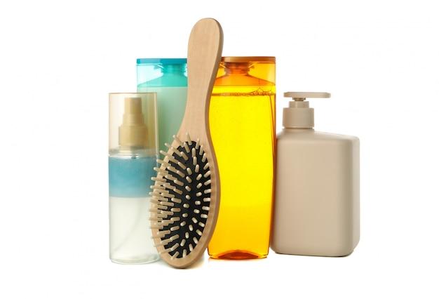 Lege cosmetica flessen en haarborstel geïsoleerd op een witte achtergrond