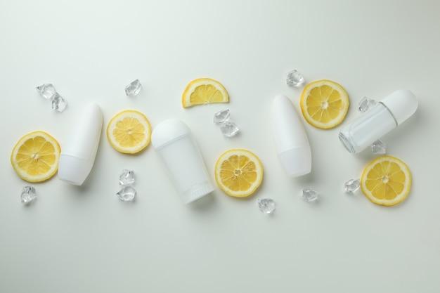 Lege deodorants, plakjes citroen en ijsblokjes op witte achtergrond