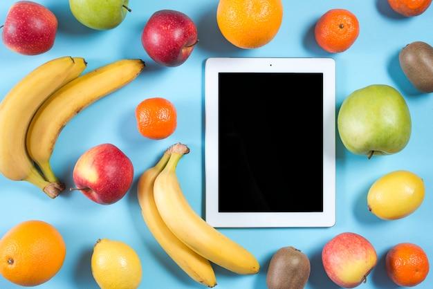 Lege digitale tablet omringd met hele gezonde vruchten op blauwe achtergrond