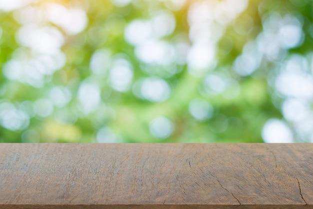 Lege donkere houten tafelblad en onscherpte aard achtergrond met copyspace voor weergave of montage van uw producten