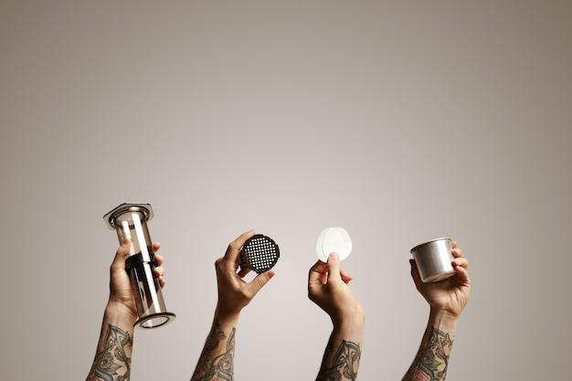 Lege doorzichtige aeropress, filterdop, twee papieren filters en stalen reisbeker in de lucht gehouden door vier handen op wit alternatieve koffiezetreclame