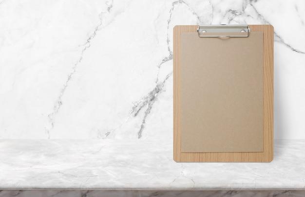 Lege eco-document blocnote op steenlijstbovenkant bij witte marmeren muur