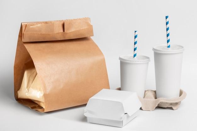 Lege fastfood-beker en hamburger-pakketten met papieren zak