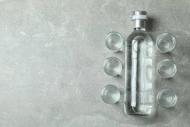 Lege fles drank en schoten op grijze muur
