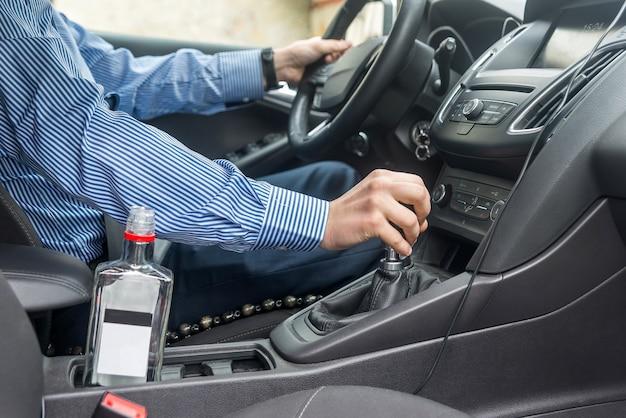 Lege fles in de buurt van de bestuurdersstoel in de auto