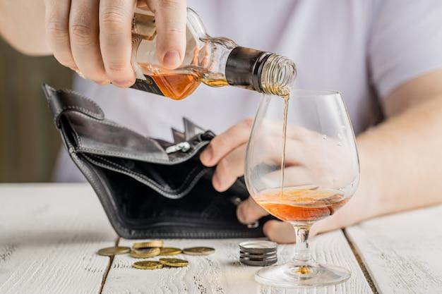 Lege fles op de achtergrond van geld. alcoholisme en armoede