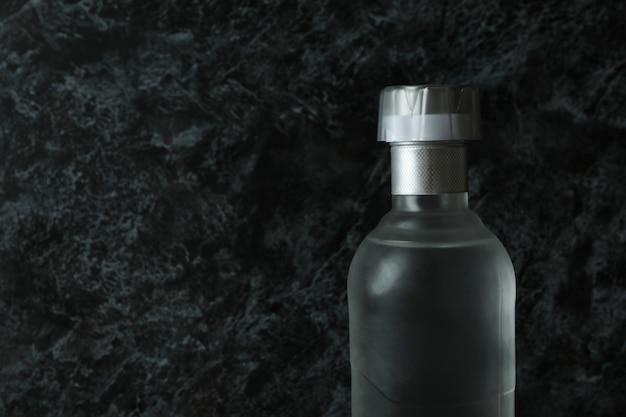Lege fles wodka op zwarte smokey oppervlak, ruimte voor tekst