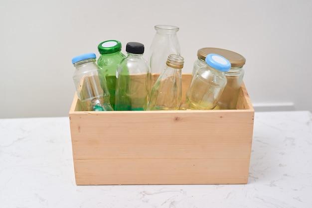 Lege flessen in houten container op tafel.