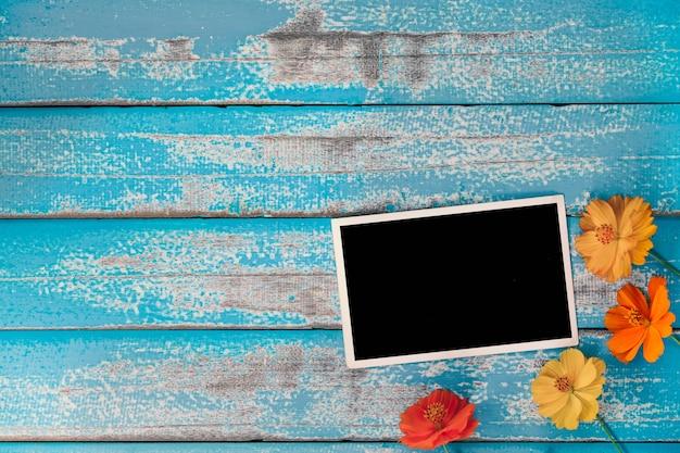 Lege foto met bloem op oude blauwe houten achtergrond