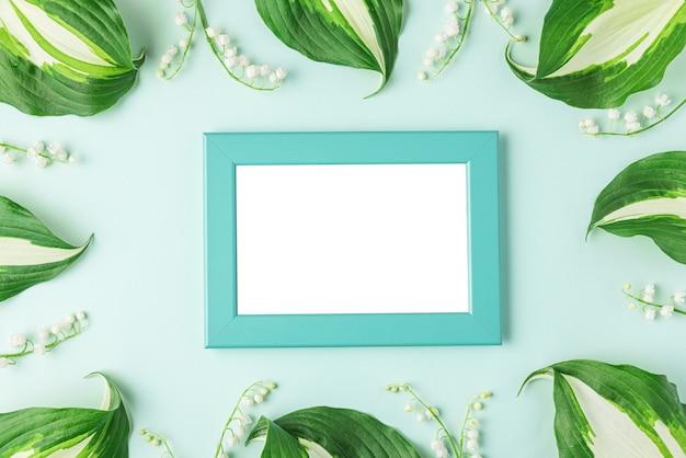 Lege fotolijst in frame gemaakt van lente lelietje-van-dalen bloemen op pastelblauw oppervlak