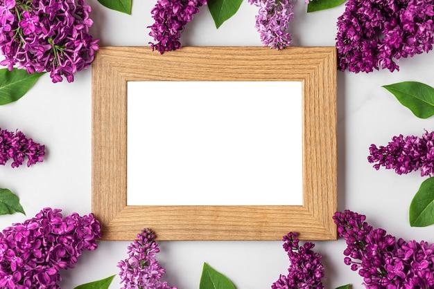 Lege fotolijst in frame gemaakt van lente lila bloeiende bloemen op witte ondergrond