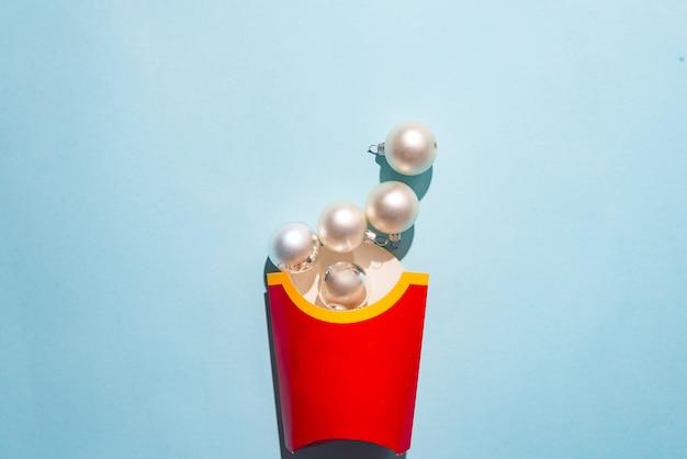 Lege frietendoos met de ballen van het witte nieuwjaar op een blauwe document achtergrond,