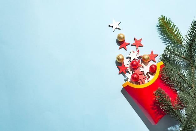 Lege frietendoos met gekleurde houten nieuwjaarssterren op een blauwe document achtergrond