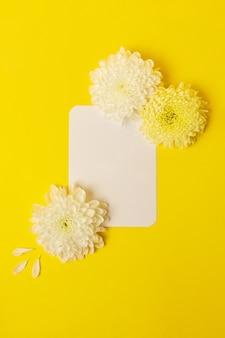 Lege geïsoleerde witte kaart op de gedurfde gele achtergrond met prachtige chrysanten erop