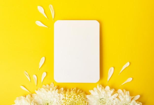 Lege geïsoleerde witte kaart op gewaagde gele achtergrond met mooie chrysanten op de achtergrond