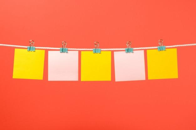 Lege gele en roze papieren notities op het touwtje