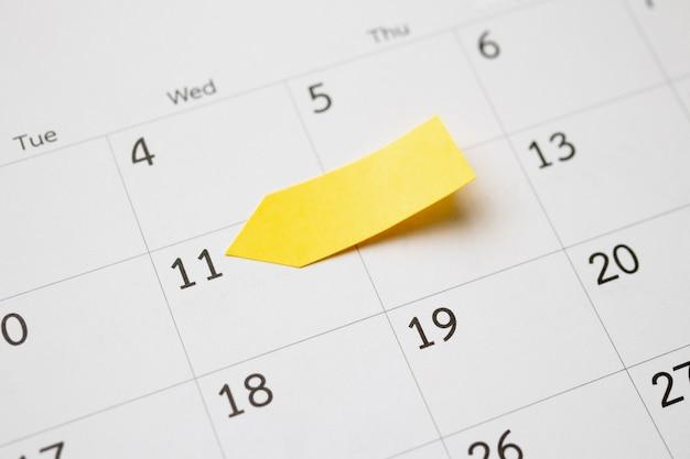 Lege gele kleverige zelfklevende postnotadocumentplanner met ruimte op de achtergrond van de kalenderpagina voor het concept van de bedrijfsplanning afspraakvergadering