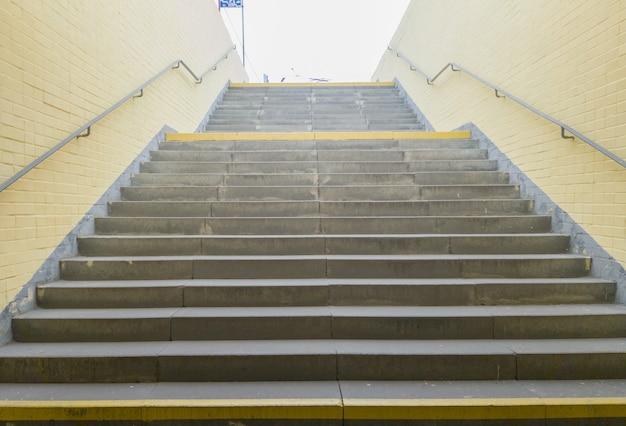Lege gele ondergrondse voetgangersoversteekplaats. tunnel en daglicht aan het einde. trap naar boven bij het zebrapad. een lange betonnen tunnel met lantaarns in de stad ondergronds.