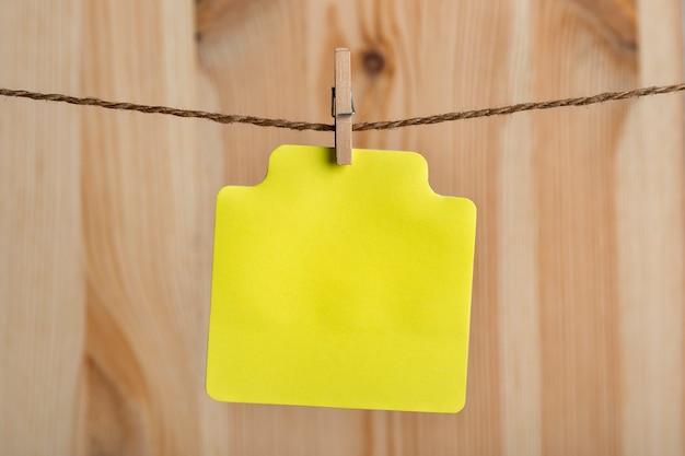 Lege gele papieren kaart hangt met wasknijper aan touw. plaats voor uw tekst. ruimte kopiëren. houten achtergrond.