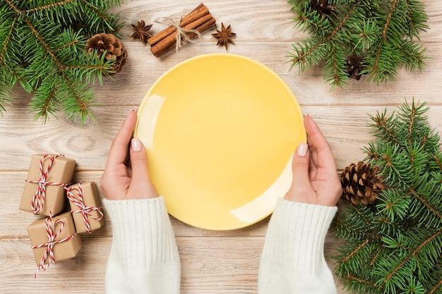 Lege gele plaat op houten oppervlak met kerstdecoratie