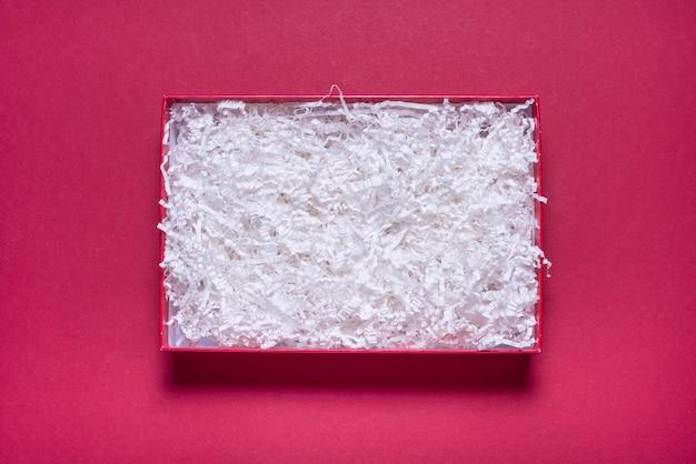 Lege geschenkdoos met papiervuller op rode achtergrond